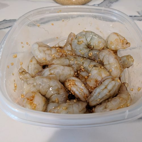 add shrimp to a small tupperware and cover with half sauce