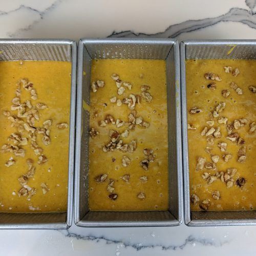 pumpkin bread pour batter into tins and top with nuts